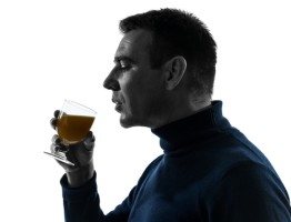 side shot of man drinking out of a glass