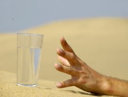 hand reaching for a glass of water in the desert
